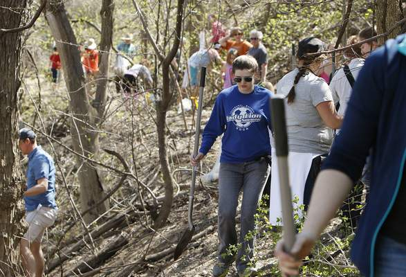 Chad Ryan | The Journal Gazette Hannah Drerer, cente,r carries a shovel as she and other volunteers plant trees and pick up garbage along the bank of the Maumee River east of the Anthony Blvd. bridge on Sunday as part of Save Maumee's Earth Day project.
