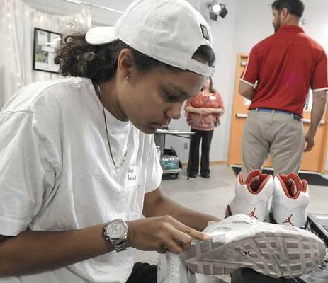 Michelle Davies | The Journal Gazette Senior Tashayla Sutorius, 17, cleans a pair of Nike Huarache shoes during Wednesday's New Tech Academy Trade Show at the City Exchange in downtown Fort Wayne.