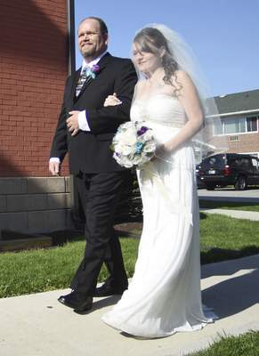 Rachel Von | The Journal Gazette Step-dad Jimy Crouse, left, walks bride Samantha Hicks to the alter during her wedding with Brandon Krontz at Shepherd's House, 519 Tennessee Ave, Fort Wayne, IN on Sunday. Brandon is a graduate of Shepherd's House and is doing very well in his recovery.