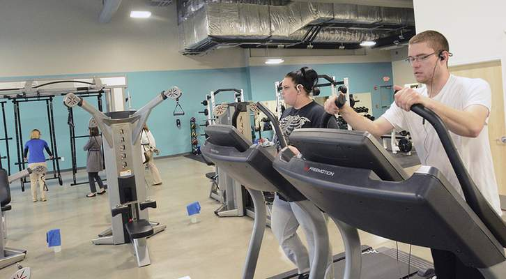 Ethan Parrish, right, and Tayor Elder work out at the Skyline YMCA while visitors take a tour of the facility Monday.