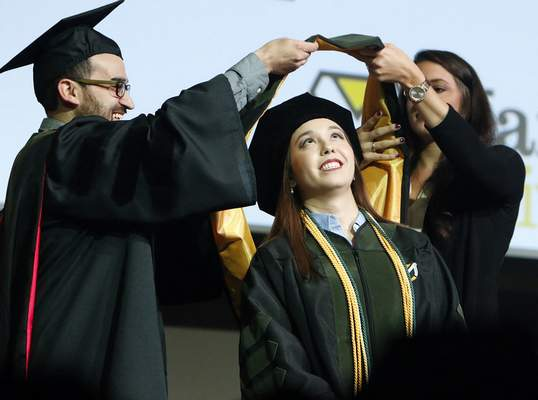 Chad Ryan   The Journal Gazette Pearl Chiyoko Pfiester, center, looks up as her mentor and assistant professor of pharmacy, Thomas Smith, left, and Alli Heeter place her hood over her head Friday. Pfiester is part of Manchester University's first class of pharmacy school doctoral graduates.