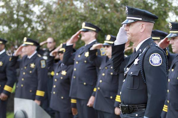 Rachel Von | The Journal Gazette Detective Martin Grooms, right, salutes during the 14th annual Police Officer Memorial Ceremony held at The Law Enforcement/Fire Fighter Memorial, 1001 North Wells Street in Fort Wayne, IN on Friday. GALLERY