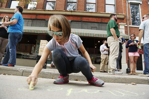 A young girl writes her name in chalk on the street at The Landing last October during a block party. The Landing is one of five revitalization projects planned by Greater Fort Wayne Inc.