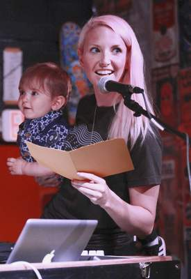 Rachel Von   The Journal Gazette Olivia Fabian holds son Arlo, 16 months, as she announces a winner of the ticket giveaway during the Middle Waves Music Festival kickoff event at The Brass Rail in Fort Wayne on Thursday.