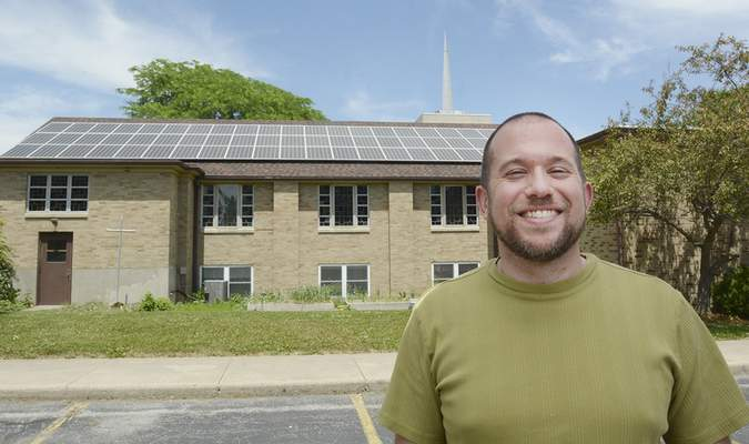 Cathie Rowand | The Journal Gazette The Rev. Brian Flory, pastor at Beacon Heights Church of the Brethren, stands near the church building, which in December had solar panels installed on its roof.