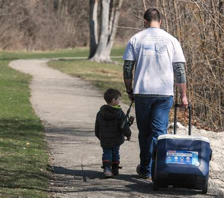 FILE: Ken White, along with his son Klay, 2, both of Fort Wayne, head down the trail around Franke Park pond to enjoy an afternoon of fishing.