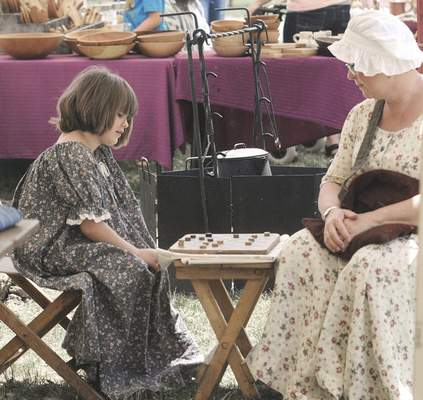 Michelle Davies   The Journal Gazette Laura Gable, right, plays draughts, more commonly known as checkers, with Ava Mauger, 6, at Sunday's celebration of Indiana's bicentennial at the Old Fort. With Video