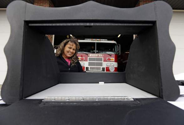FILE - In this file photo taken on Thursday, Feb. 26, 2015, Monica Kelsey, firefighter and medic who is president of Safe Haven Baby Boxes Inc., poses with a prototype of a baby box, where parents could surrender their newborns anonymously, outside her fire station in Woodburn, Ind. Kelsey, founder of the organization, said she is undeterred by a warning from Indiana that they are illegal. (AP Photo/Michael Conroy, File)