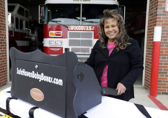 FILE - In this file photo taken on Thursday, Feb. 26, 2015, Monica Kelsey, firefighter and medic who is president of Safe Haven Baby Boxes Inc., poses with a prototype of a baby box, where parents could surrender their newborns anonymously, outside her fire station in Woodburn, Ind. Kelsey said she is undeterred by a warning from Indiana that they are illegal. (AP Photo/Michael Conroy, File)