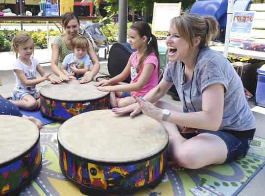 Photos by Michelle Davies | The Journal Gazette Ali Dencklau, with Happy Keys, laughs as she drums with children Tuesday at Freimann Square downtown as part of Make Music Day.