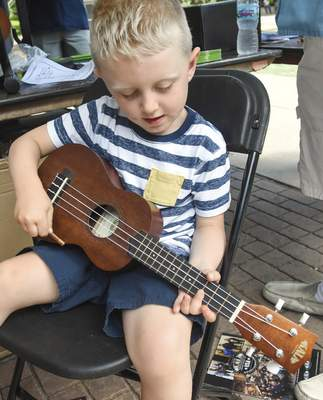 Noah Kaler, 4, of Fort Wayne, tries his hand at playing a ukulele. Sponsored by Sweetwater Sound, the event included interactive instrument demonstrations as well as a variety of performances.