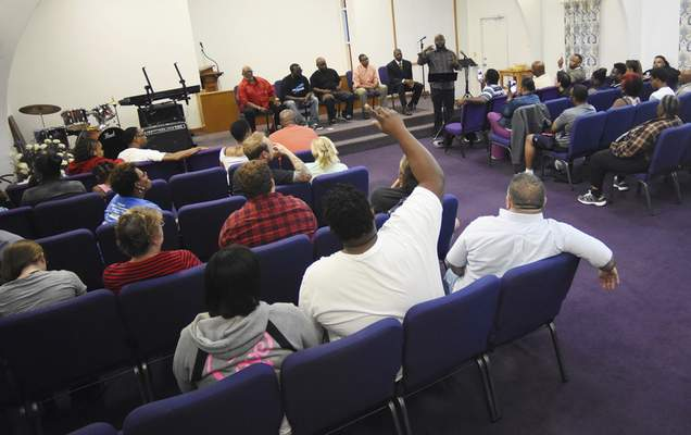Photos by Rachel Von | The Journal Gazette The Rev. Carlton A. Lynch speaks as Andrew Woodson raises his hand from the crowd during a meeting about youth violence at New Beginnings Church on Sunday.