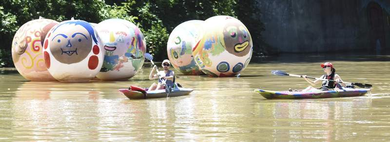 Photos by Michelle Davies   The Journal Gazette Kayakers on the St. Marys River on Wednesday pass in front of giant beach balls painted for the Faces of the Fort celebration. The event runs 6 to 8 p.m. today on the Historic Wells Street Bridge.