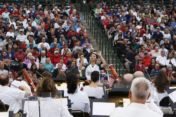Photos by Chad Ryan | The Journal Gazette Conductor Chia-Hsuan Lin leads the Fort Wayne Philharmonic during Sunday's Patriotic Pops concert in front of more than 7,000 people at Parkview Field.