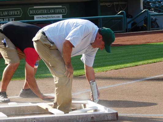 Brian Francisco | The Journal Gazette U.S. Sen. Joe Donnelly, D-Ind., spray-paints the batter's boxes Tuesday before the TinCaps game at Parkview Field.