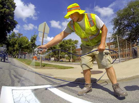 File: A worker with the city Traffic Engineering Department paints part of the crosswalk at Jefferson Boulevard and Union Street.