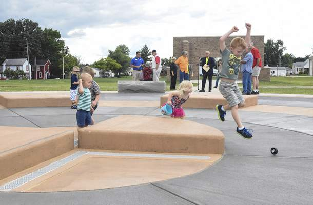 Photos by Michelle Davies | The Journal Gazette Children run around the splash pad area of the Franklin School Park before the grand opening Thursday afternoon. The historic architecture of the old school was restored as part of the project.