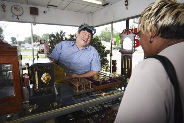 Photos by Rachel Von | The Journal Gazette Jim Hansen helps Linda Oliver at The Clock Shoppe on Lower Huntington Road. Hansen has always been fascinated with clocks, leading him to purchase the clock shop in 2013.