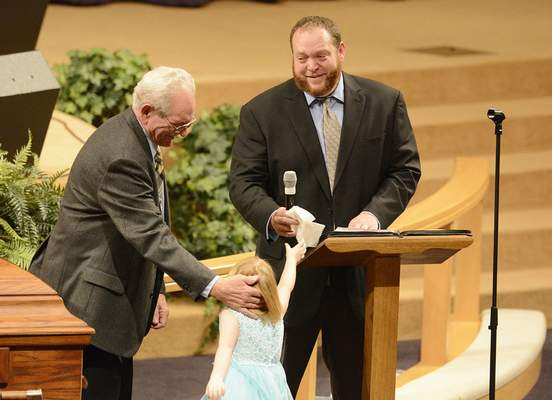 Chad Ryan | The Journal Gazette Gerald Vandeveer, right, smiles as his daughter hands him a tissue during an emoitonal moment as he delivers his comments about his mother, Linda Vandeveer, during her funeral services on Monday at First Assembly of God church on Washington Center Road. Vandeveer and her husband Jerry, left, worked with local law enforcement clean up their neighborhood of crime and drug houses and helped build the Law Enforcement/Firefighters Memorial on Wells Street.