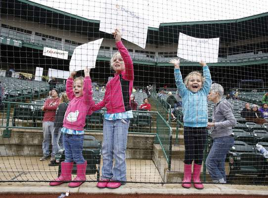 Photos by Chad Ryan   The Journal Gazette Caroline, 3, Olivia, 8, and Sydney Bessesen, 6, cheer for their mother, Mary, as she crosses the finish line at Parkview Field.