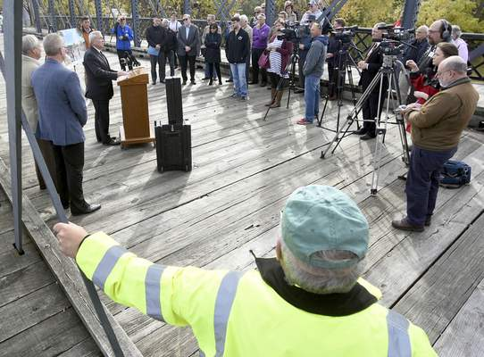 Rachel Von   The Journal Gazette Community leaders and the media listen to Mayor Tom Henry during a press conference on the update on riverfront development efforts in the city of Fort Wayne at the Historic Wells Street Bridge on Monday.