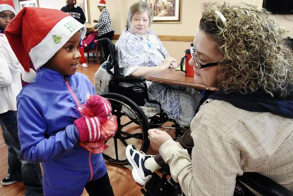 Cathie Rowand | The Journal Gazette Princess Chew, 5, gives cookies to Mary Drew during a visit Thursday to Summit City Nursing & Rehabilitation. Children passed out cookies, sang Christmas songs – and received new winter coats.