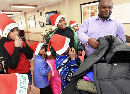 Cathie Rowand | The Journal Gazette Patrick Ngene, director of Summit City Nursing & Rehabilitation, passes out coats to children from the after-school program at Greater Progressive Baptist Church's Family Life Center.