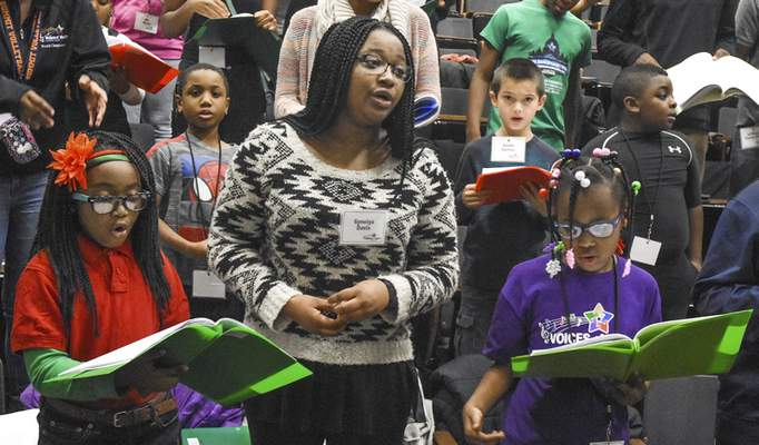 Choir members, from left, MaKiyah Bates, 8, Gyneiya Davis, 16, and El'Laira Winborn, 8, sing during rehearsal.