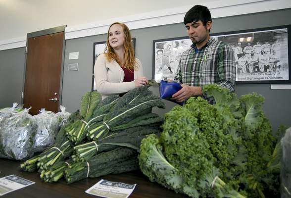 Master Plan Farms' Allie Beck, left, and Matt Baker count change for a customer. In the winter, the market features a different variety of produce.