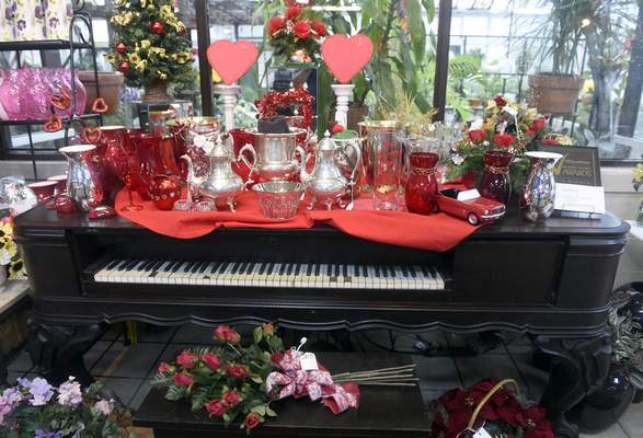 Valentine's Day items are displayed on top of the 1879 Decker & Son square grand piano once owned by Joan Schmitt's great-great-grandmother at The Flower Shop in Evansville.