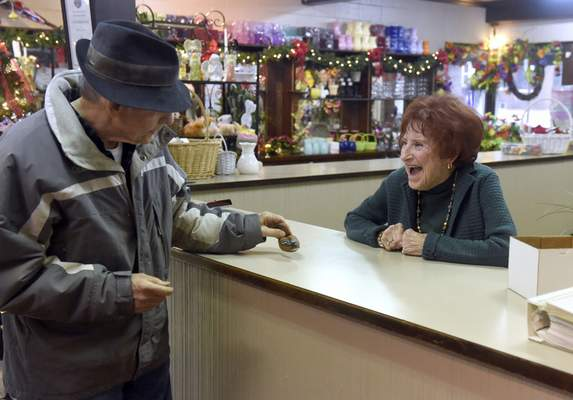 Associated Press photos Owner Joan Schmitt jokes with longtime customer Wayne Kinch while working at The Flower Shop in Evansville. At age 90, she's ready to walk away.
