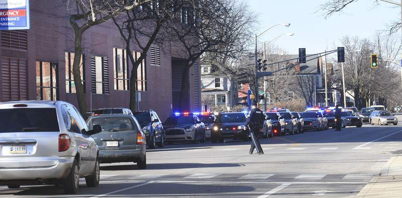 Cathie Rowand | The Journal Gazette Fort Wayne police and Allen County Sheriff's Department officers escort an Allen County police officer from St Joseph Hospital Monday morning. The officer died while on duty Sunday night during a medical emergancy, the sheriff's department said.