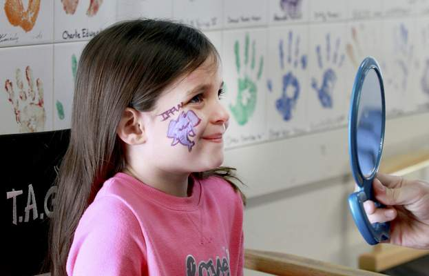 Baylee Bertsch, 6, reacts to seeing an IPFW mastodon from T.A.G. Art's Michael Ganser on her face Saturday.