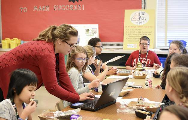 Rachel Von | The Journal Gazette Lizzie Pope, adviser for the Early Act Club at Holland Elementary, helps students during a recent lunchtime club meeting.