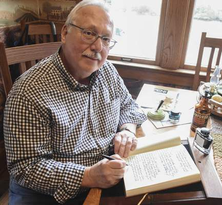 Photos by Michelle Davies | The Journal Gazette John Reche of Fort Wayne writes on a traveling desk from the 1880s in a journal with a Esterbrook dip pen. Reche is an avid collector of fountain pens.