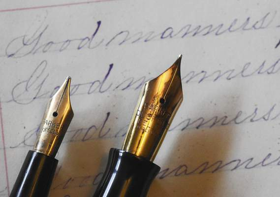 Reche's collection includes, left, an 1898 Parker eye dropper fountain pen and a 1930s Parker Duofold fountain pen, shown on a sample of a student's handwriting practice book from the 1870s.