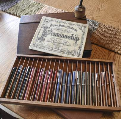 A tray of vintage Esterbrooks, a circa 1880s traveling desk, antique ink bottle and dip pen and a penmanship book are just a few of the fountain pen items collected by Reche.