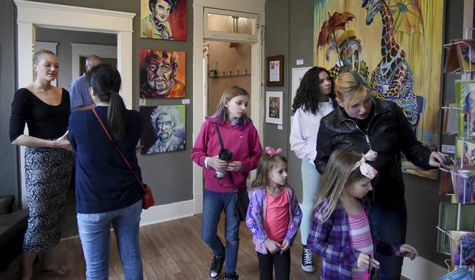 Rachel Von | The Journal Gazette Artist Alex Hall, left, talks with guests as they browse her art in her studio during the Art on Broadway event Saturday.
