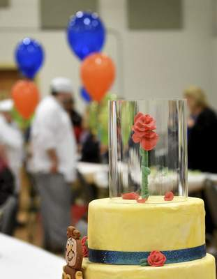 "Samuel Hoffman | The Journal Gazette A rose tops a ""Beauty and the Beast""-themed cake at Ivy Tech's 11th annual Edible Book Festival. Entries included cakes for ""Harry Potter"" and ""War and Peace."""