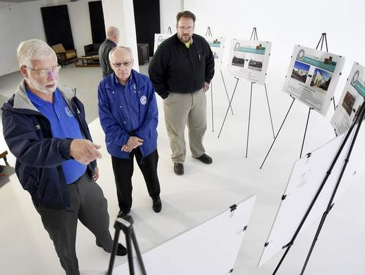Samuel Hoffman | The Journal Gazette Jack Dunifon, left, and Frank Oddou of St. Vincent de Paul, and Todd Ziegler of Ziegler's Window Coverings, check the artist renderings of their new business fronts at the announcement of the 2017 facade grants, at Punch Films studios, Thursday.