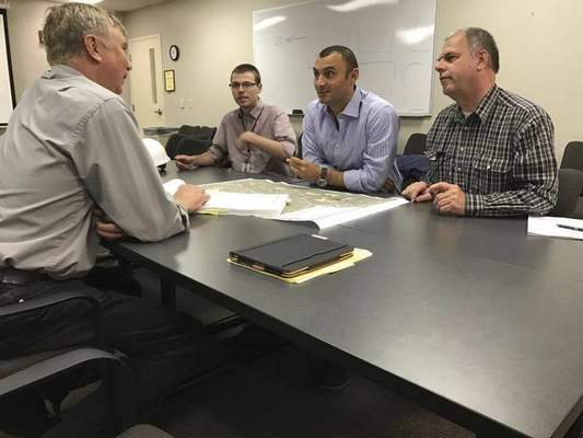 Dave Gong | The Journal Gazette Salini Impregilo and S.A. Healy managers Claudio Cimiotti, center, and Manfred Lechner, right, discuss the Three Rivers Protection and Overflow Reduction Tunnel with City Utilities' Mark Gensic, left, and Zak Katter, top.