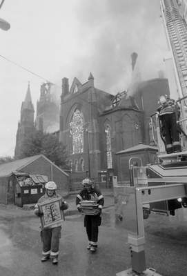 File Sept. 2, 1993: Firefighters carry items out of St. Mary's Catholic Church downtown.