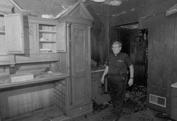 File Sept. 2, 1993: Father Tom O'Conner walks through a burned section of St. Mary's Catholic Church.