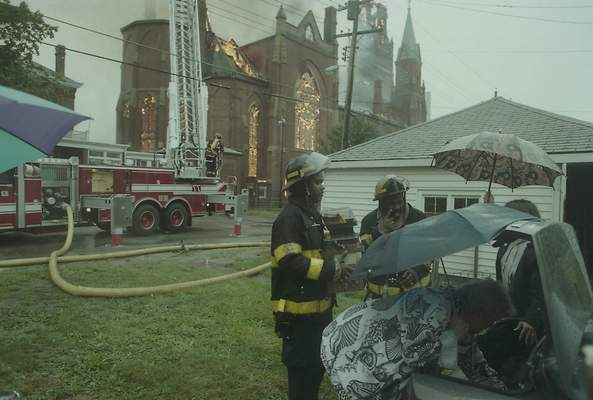 File Sept.2, 1993: Firefighters help put files saved from the church in the trunk of a car.