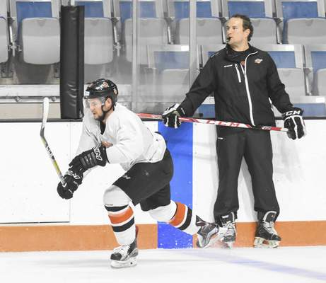 Michelle Davies | The Journal Gazette Komets coach Gary Graham, right, directs practice as Mike Embach skates by at Memorial Coliseum. Graham will be back for a fifth season with the Komets, who will only be able to keep four of their seven veteran skaters, a list that includes Embach.