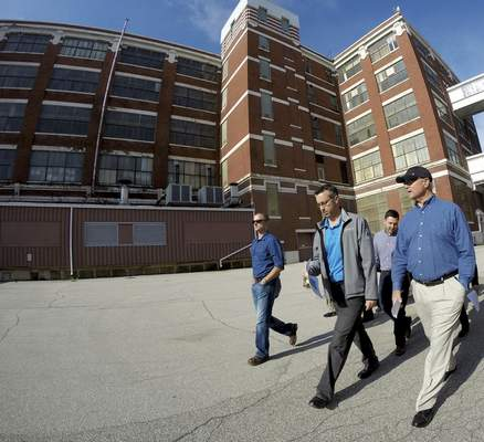 Rachel Von | The Journal Gazette Downtown Improvement District's Bill Brown, right, and Elevatus' Cory Miller walk through the campus during a Greater Fort Wayne Inc. tour through six buildings on the GE campus on May 26.