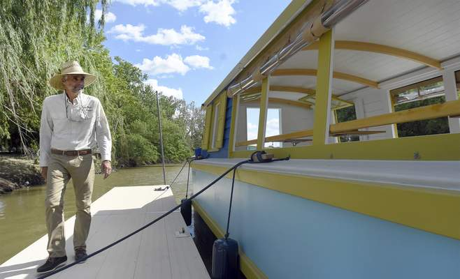 Dan Wire checks out the boat during the canal boat christening event at Headwaters Park West on Tuesday. The event included guest speakers, boat tours, and rotary singers, the unveiling of the official boat name Sweet Breeze.