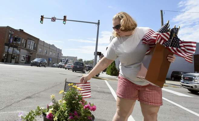 Rachel Von | The Journal Gazette Madalyn Sade-Bartl, clerk-teasurer for Churubusco and project manager for the Stellar Communities Designation Program, places a flag in a flower pot along Main Street in Churubusco on Friday. Churubusco is one of three finalists in the program. One city will be selected to receive a prize of $6 million for community development.