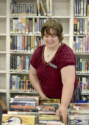 Rachel Von | The Journal Gazette Library director Rachel Eyermann works on straightening books that are part of the book sale at the Churubusco Public Library on Friday.