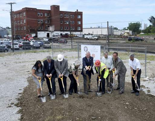 Mayor Tom Henry, center, leads the first ceremonial groundbreaking for the Three Rivers Protection and Overflow Reduction Tunnel (3RPORT) Thursday at Glasgow and Dwenger avenues. S.A. Healy and Salini Impregilo will construct the 5-mile long tunnel, 200 feet below the surface, to reduce by 90% the number of combined sewer overflows on the rivers. The tunnel will start behind the former Wayne Pump building, left, which will be razed.